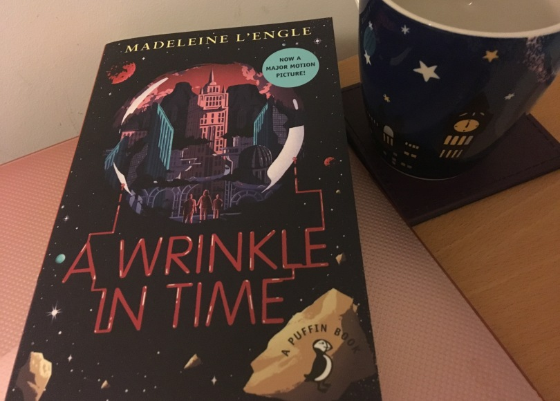 "cover of a Puffin Book edition of Madeleine L'Engle's novel ""A Wrinkle in Time"", photographed next to a mug with a clock depicted on it."