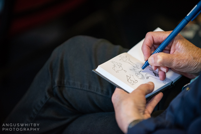 A conference attendee taking notes by drawing images of fish during Perry Nodelman's keynote, fish is people