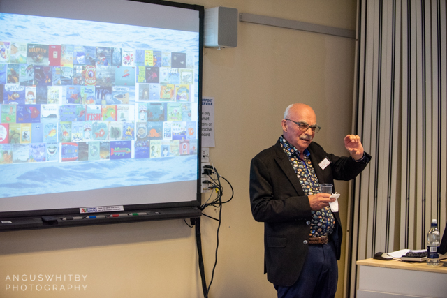 Perry Nodelman, presenting his keynote, Fish is people, demonstrating just how many picturebooks there are about fish